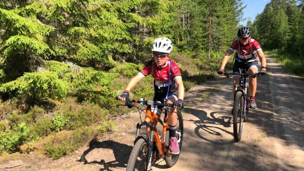 Nelly och Cici cyklar mountainbike på grusväg