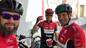 Tre personer som dricker kaffe i cykelkläder.